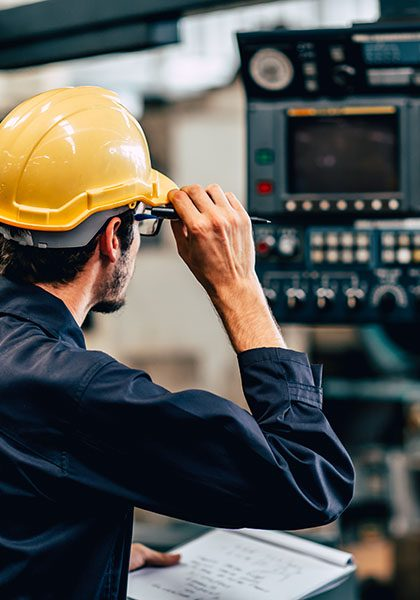 Specialized-Business-Insurance-Worker-in-Hard-Hat-Checks-Equipment-In-A-Manufacturing-Plant